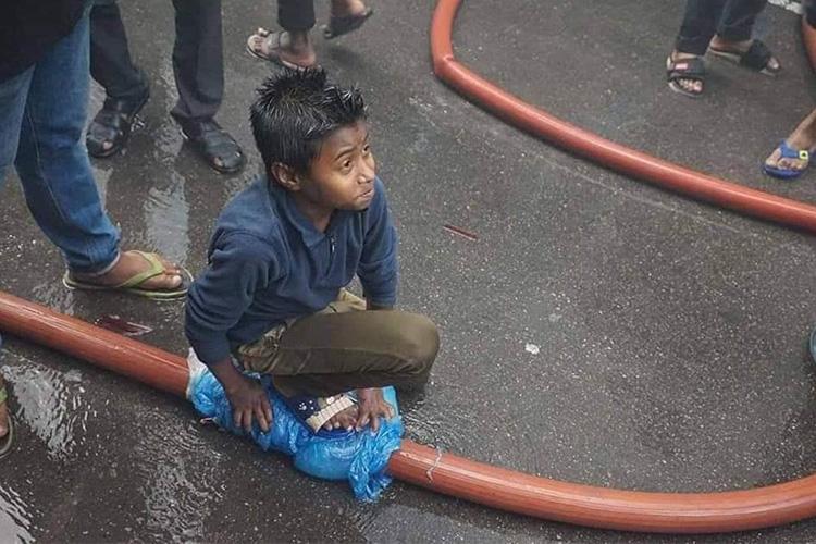 ফায়ার সার্ভিসের ফেটে যাওয়া পানির পাইপ চেপে ধরে আছেন ১০ বছরের নাঈম/ ছবি: সংগৃহীত