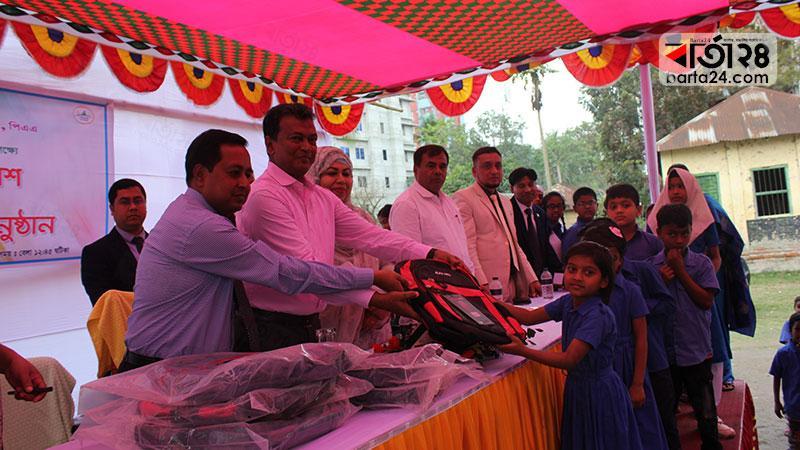 শিক্ষার্থীদের মাঝে নতুন স্কুল ব্যাগ বিতরণ করছেন ঢাকা বিভাগীয় কমিশনার। ছবি: বার্তা২৪.কম